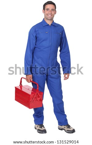 Man wearing blue overalls holding tool kit - stock photo