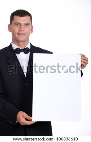 Man wearing bow-tie holding white board - stock photo