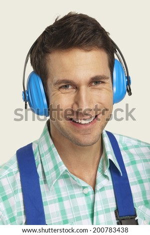 Man wearing ear muff smiling close-up - stock photo