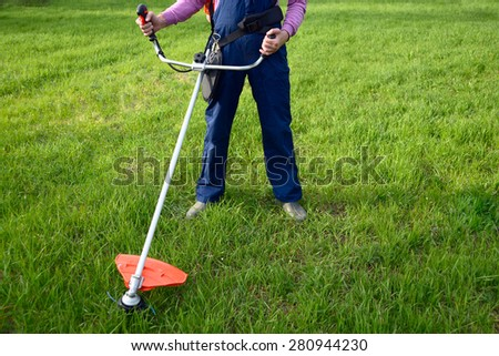 Man wearing ear protectors and glasses mowing grass with petrol weed trimmer - stock photo