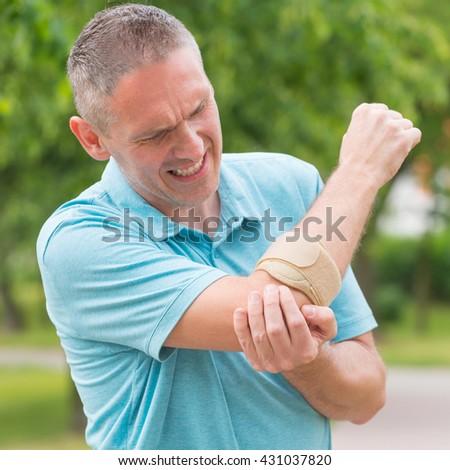 Man wearing elbow brace to reduce pain - stock photo