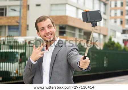 Man wearing formal clothing posing with selfie stick in urban environment smiling using right hand to make a signal. - stock photo