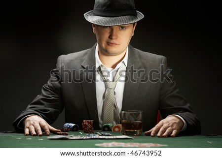 man wearing hat is playing poker in casino