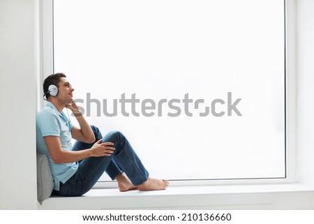 Man wearing headphones at the window - stock photo
