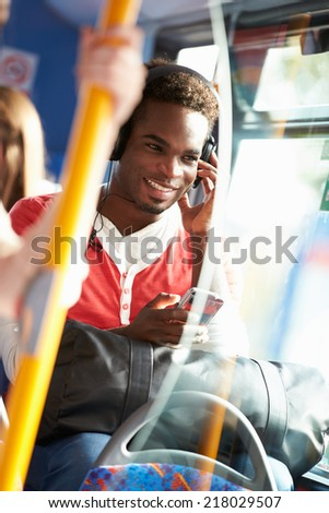 Man Wearing Headphones Listening To Music On Bus Journey