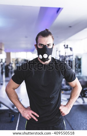 Man wearing High Altitude Mask Fitness Training. Depth of field, motion blur, selective focus, focus on man's eyes - stock photo