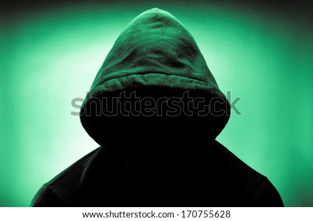 Man wearing hood with face in shadow - stock photo