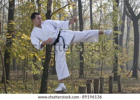 Man wearing  (Karate uniform) and black belt shown in a kick - stock photo