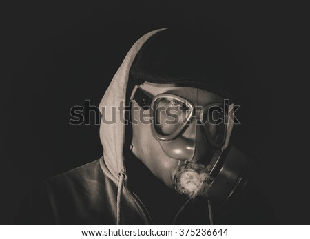 Man wearing mask and smoking,low key and monochrome - stock photo