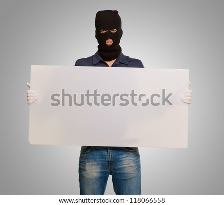 Man wearing mask holding a blank card isolated on gray background