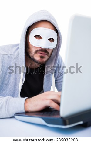 Man wearing mask while hacking into laptop on white background - stock photo