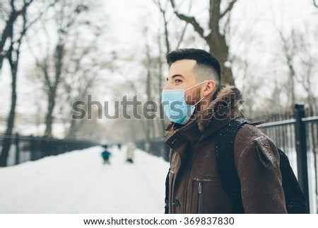 Man wearing medical face mask in the Park . Male wearing face mask, protection from virus infection in winter time. - stock photo