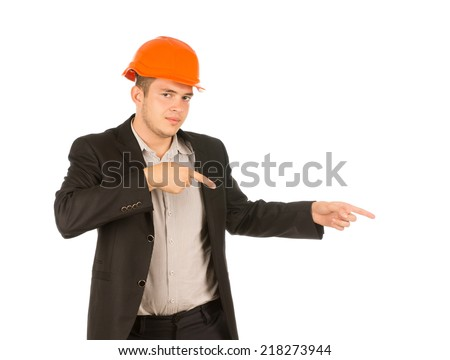 Man Wearing Orange Hard Hat and Suit Jacket Pointing to the Side and Looking at the Camera - stock photo