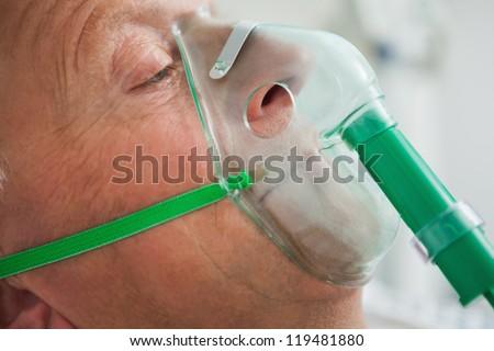 Man wearing oxegen mask in hospital - stock photo