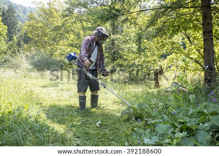 Man wearing protective helmet with goggles to shield his eyes while trimming the lawn with weed eater surrounded with green trees.