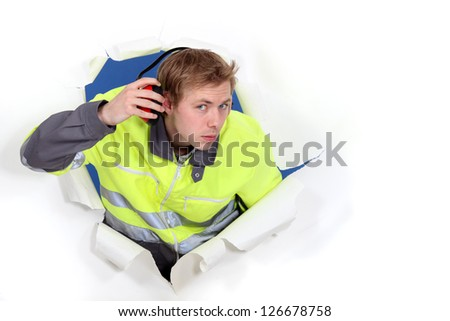 Man wearing reflective jacket and hearing protection - stock photo