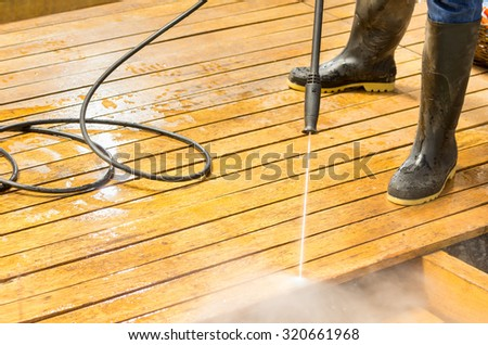 Man wearing rubber boots using high water pressure cleaner on wooden terrace surface.