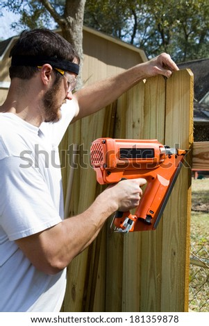 Man wearing safety glasses uses a portable nail gun to attach wood pickets to the rail as he builds a privacy fence in the backyard. - stock photo