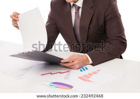 Man wearing suit sitting in desk observing pile of charts - stock photo