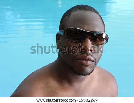 Man Wearing Sunglasses with a blue water background - stock photo