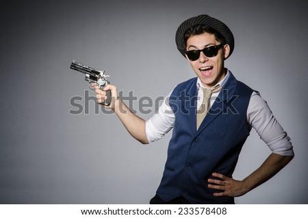 Man wearing sunglasses with gun - stock photo