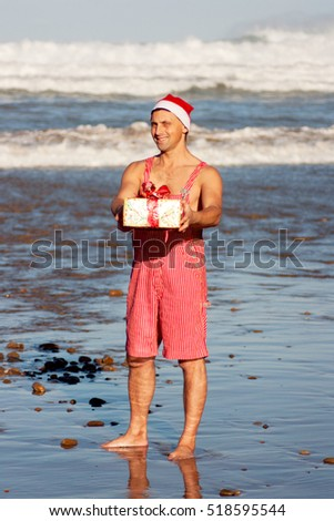 Man wearing the christmas hat standing with gift on the beach