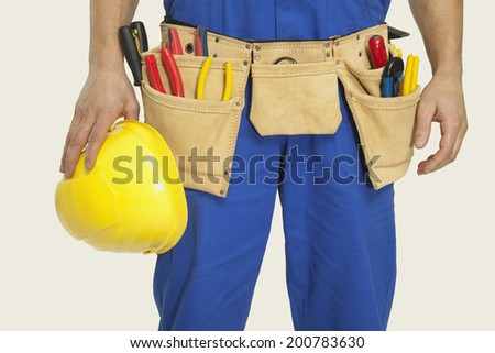 Man wearing tool belt and holding hardhat mid section close-up - stock photo