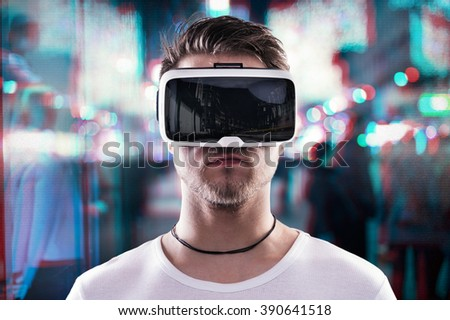 Man wearing virtual reality goggles against night city - stock photo