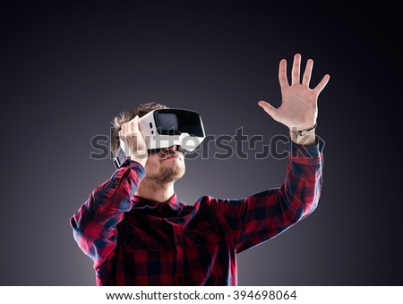 Man wearing virtual reality goggles. Studio shot, black backgrou - stock photo
