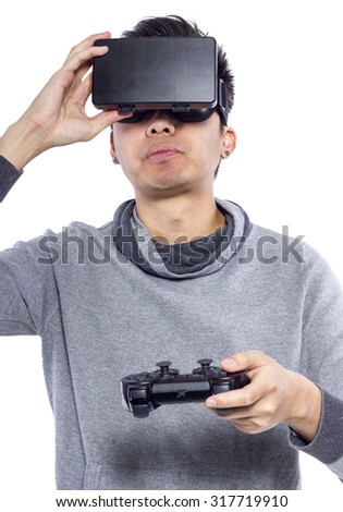 Man wearing virtual reality goggles watching movies or playing video games.  He is isolated on a white background.  The vr headset design is generic and no logos. - stock photo