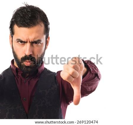 Man wearing waistcoat doing a bad signal - stock photo