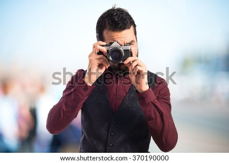 Man wearing waistcoat photographing on unfocused background