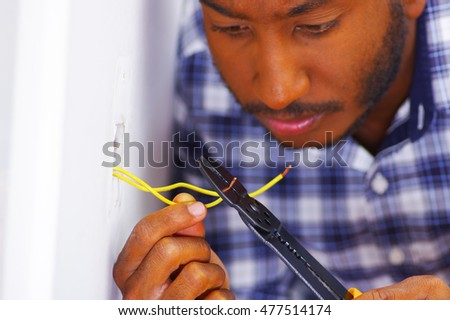 Man wearing white and blue shirt working on electrical wall socket wires using screwdriver, electrician concept.