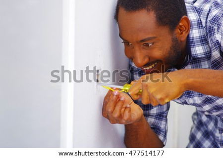 Man wearing white and blue shirt working on electrical wall socket wires using screwdriver, concentrated facial expression.