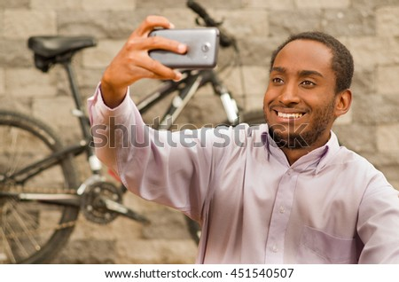 Man wearing white red business shirt sitting down, holding up mobile phone taking selfie photo, smiling and posing, bicycle standing behind leaning against grey brick wall