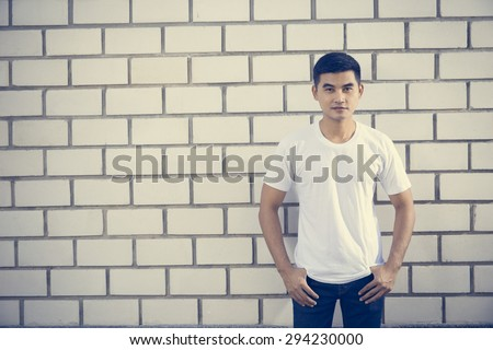 man wearing white t-shirt on brick wall background, process color - stock photo