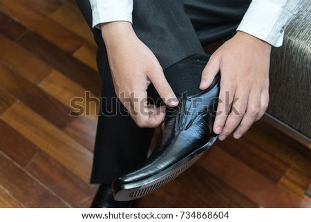Man wears leather shoes in morning wedding preparations or business work
