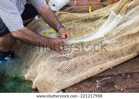 Man weaving fishing net, fishing industry - stock photo