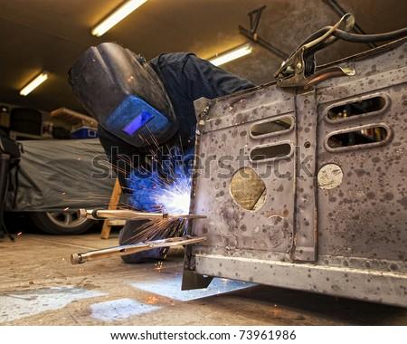 Man Welding Truck Frame - stock photo