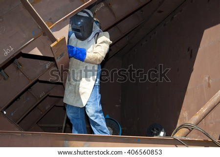 Man welding wearing protective clothes and equipment
