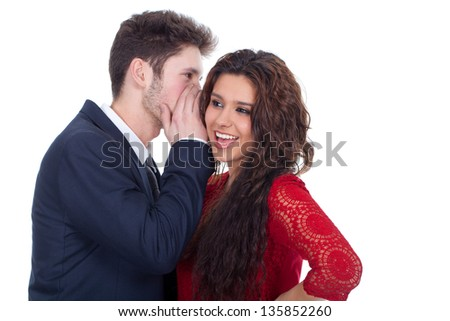 Man whispering a secret to a surprised young lady - stock photo