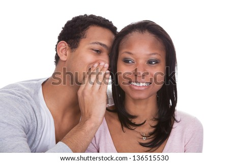 Man Whispering To Girlfriend's Ear Over White Background - stock photo