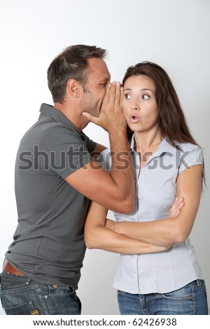 Man whispering to his girlfriend ear - stock photo