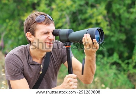 Man who is watching in spotting scope. Positive man looking through a telescope  - stock photo