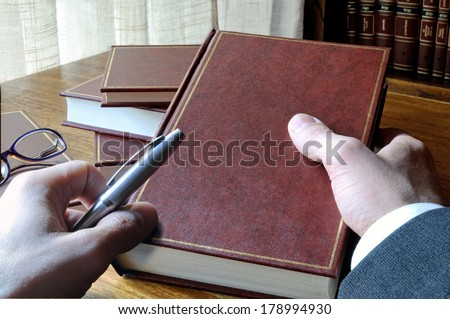 man who will take notes from a book, with window and library background - stock photo