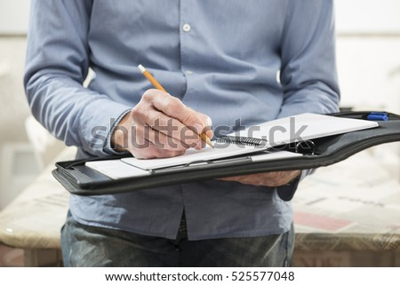 man who writes notes on notebook in office