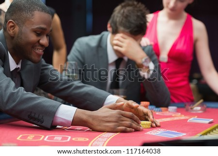 Man winning jackpot as other man is being comforted by woman at poker table in casino - stock photo