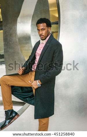 Man Winter Fashion in New York. African American Businessman wearing dark gray woolen overcoat, pink undershirt, yellow pants, black leather boot shoes, bow tie, standing by metal structure, thinking.