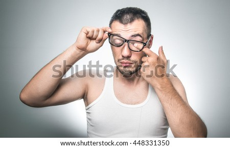 Man wiping eyes with his fingers, isolated on gray background. Waking morning. Guy with undershirt holding eyeglasses