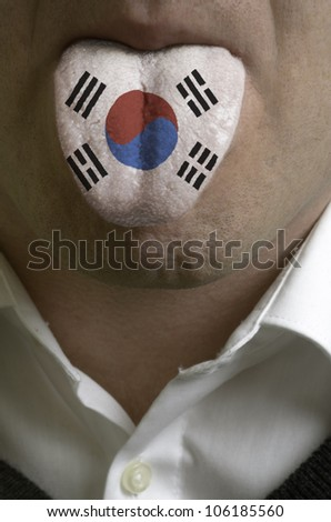 man wit open mouth spreading tongue colored in south korea flag as symbol of values like teaching, learning, multilingual speaking of different languages - stock photo